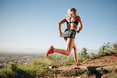 Photo for Rear view of a woman in fitness wear sprinting. Female athlete training outdoors running on a sunny day. - Royalty Free Image