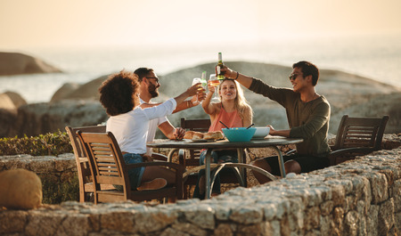 Photo pour Four friends toasting drinks sitting on a dining table outdoors near the seashore. Multiethnic friends on a holiday having fun drinking wine and snacks. - image libre de droit