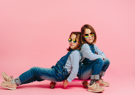 Photo pour Stylish twin girls sitting together on a skateboard. - image libre de droit
