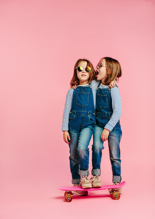 Photo pour Twin girls wearing fashion clothes with skateboard on pink - image libre de droit