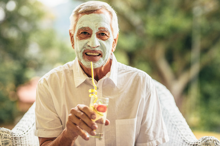 Photo pour Funny elderly man with clay mask on face drinking juice. Retired senior man at home taking care of his skin at old age. - image libre de droit