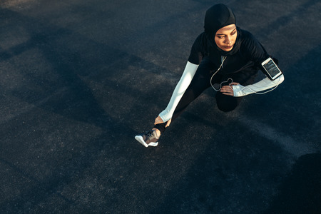 Photo pour Healthy muslim woman with hijab doing exercise in morning. Hijab girl doing leg stretching workout on the street. - image libre de droit