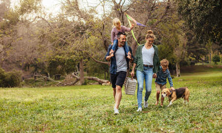 Photo pour Happy couple with their two children and dog walking in park. Man carrying little girl with kite on shoulders and woman carrying a picnic basket with son and pet dog. - image libre de droit