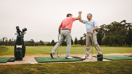Photo for Senior golfers high five at driving range. - Royalty Free Image