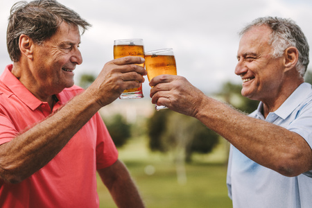 Foto de Two senior men toasting beer glasses outdoors. Smiling mature male friends cheering beers while standing outside. - Imagen libre de derechos