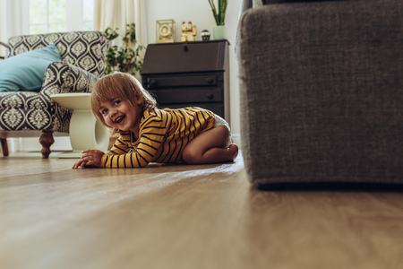 Photo for Smiling kid sitting on floor at home. Cheerful kid hiding behind a couch playing hide and seek. - Royalty Free Image