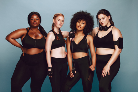 Foto de Group of women of different race and body size dressed in sportswear standing together against grey background. Diverse women in sports clothing looking at camera. - Imagen libre de derechos