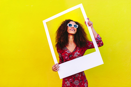 Foto de Pretty woman in a red dress and sunglasses standing against a yellow wall and holding a large empty frame. - Imagen libre de derechos