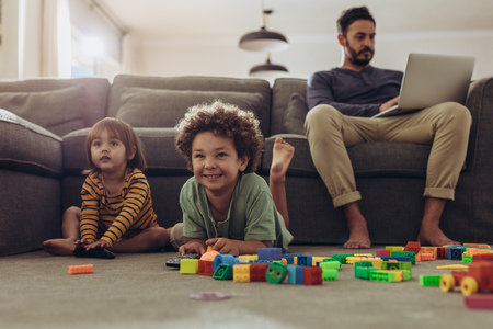 Photo pour Smiling kids playing with building blocks and watching television at home. - image libre de droit