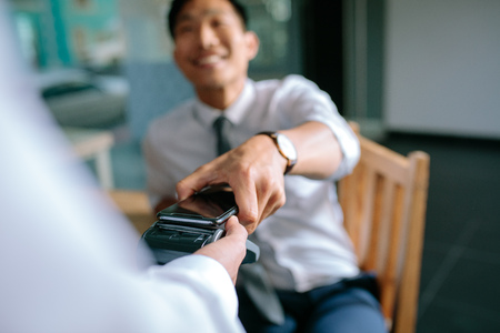 Photo pour Businessman paying bill through smartphone using NFC technology in restaurant. Closeup of male hand holding his mobile phone over a card reader machine for doing the payment. - image libre de droit