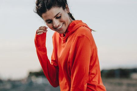 Photo pour Smiling sportswoman in tracksuit standing outdoors. - image libre de droit