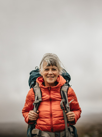 Photo for Smiling woman hiker wearing jacket and backpack on a hiking trip. Adventure seeking woman walking on a hill on a cloudy day. - Royalty Free Image