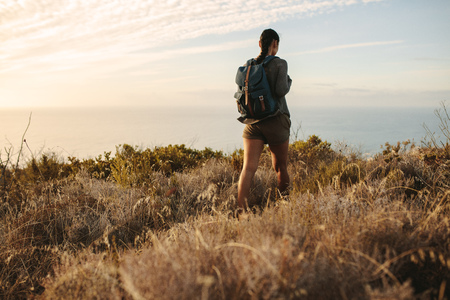 Photo for Rear view of woman walking on a mountain trail. Woman walking on a countryside rocky hill with a backpack. - Royalty Free Image