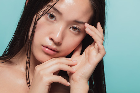 Foto de Close up of young asian woman with beautiful skin. Female model with fresh and healthy skin looking at camera. - Imagen libre de derechos