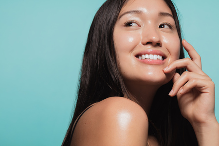 Foto de Close up of cute asian girl with glowing skin against blue background. Beautiful face of girl with fresh healthy skin. - Imagen libre de derechos