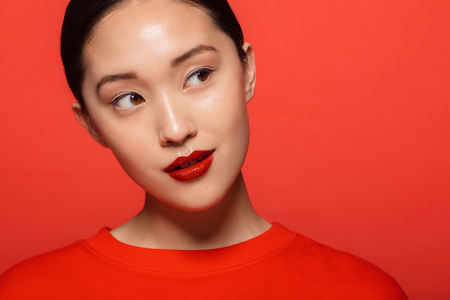 Foto de Close up of young asian woman with beautiful make up looking away and thinking. Korean female model with red make up against red background. - Imagen libre de derechos