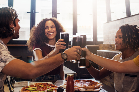 Foto de Smiling young men and women sitting inside a restaurant toasting soft drinks. Multi-ethnic group of people toasting cold drinks with pizza on table at restaurant. - Imagen libre de derechos