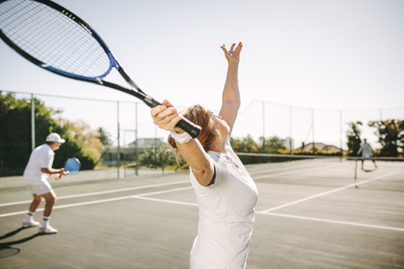 Photo for Rear view of a woman serving the ball while playing a mixed doubles tennis match. Men and women playing tennis outdoors on a sunny day. - Royalty Free Image