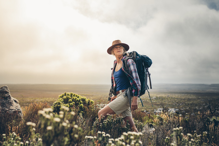 Photo for Senior woman standing on a hill wearing a backpack and looking away. Adventure seeking woman trekking through the bushes on a hill. - Royalty Free Image