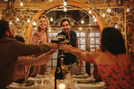 Photo pour Host couple toasting drinks with guest at dinner party. Young cheerful people celebrating with drinks at party. - image libre de droit