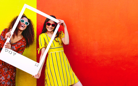 Foto de Portrait of two women holding a blank photo frame in hand and smiling. Girls wearing sunglasses standing against red and yellow colored wall. - Imagen libre de derechos