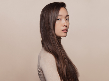 Foto de Portrait of beautiful young woman with long brown hair standing against beige background. Asian woman with a long straight hair looking at camera. - Imagen libre de derechos