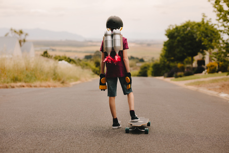 Photo pour Rear view of young boy with helmet and toy jetpack standing with his skateboard and looking down the road. Jetpack boy with skateboard - image libre de droit