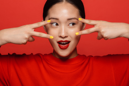 Foto de Close up portrait of young asian woman with beautiful make up looking through fingers on red background. - Imagen libre de derechos