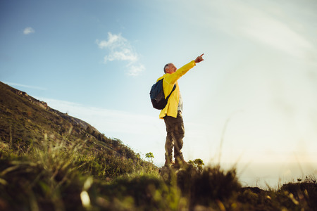Photo for Senior man standing on a hill wearing a backpack and pointing at the sky. Adventure seeking man standing on top of a hill looking away. - Royalty Free Image