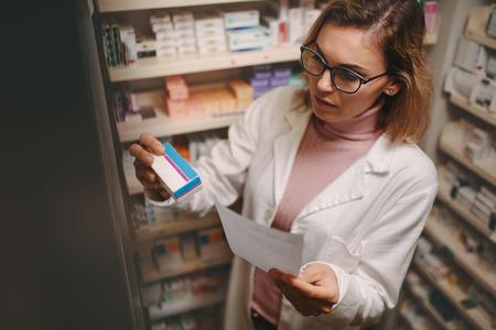 Foto de Chemist with a prescription searching right medicine on shelves in pharmacy. Female pharmacist holding prescription checking medicine in pharmacy. - Imagen libre de derechos