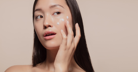 Photo pour Close up of a youthful female model applying moisturizer to her face. Young korean woman applying moisturizer cream on her pretty face against beige background. - image libre de droit