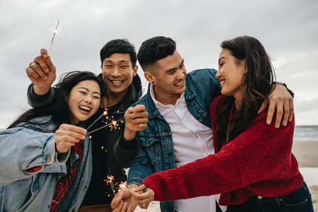 Photo pour Diverse group of young people celebrating new year's day at the beach. Young asian people having fun with sparklers outdoors at the sea shore. - image libre de droit
