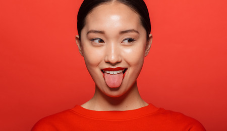 Photo pour Close up of young asian woman sticking out tongue and looking away. Korean female model making funny face against red background. - image libre de droit