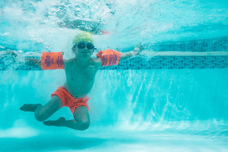 Photo for Underwater shot of a boy with sleeve floats in the pool. Child learning to swim in a swimming pool. - Royalty Free Image