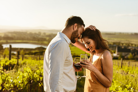 Foto de Couple on a romantic date standing together drinking red wine in a wine farm. Couple on a wine date spending time together. - Imagen libre de derechos