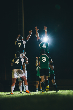 Photo pour Rugby players jumping for line out at the stadium. Teams jumping for possession of the ball during rugby match. - image libre de droit