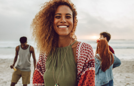Foto de Attractive african woman on the beach smiling at camera. Pretty young female standing at the beach with group of friends in background. - Imagen libre de derechos