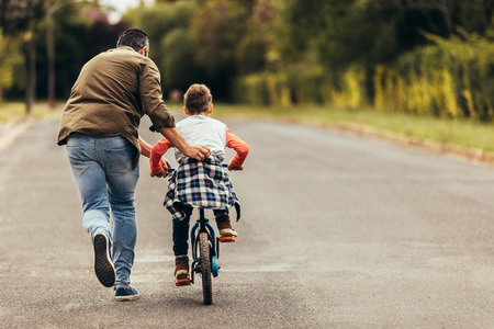 Photo pour Rear view of a boy riding a bicycle while his father runs along holding the kid. Father teaching his son to ride a bicycle. - image libre de droit