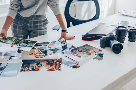 Photo for Woman standing at her desk and choosing the best images from photoshoot. Female photographer looking at the photo prints on table. - Royalty Free Image