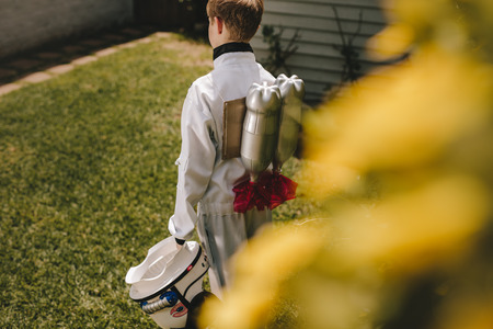Photo pour Rear view of boy in space suit carrying a toy jetpack on his back. Boy pretending to be an astronaut playing in backyard. - image libre de droit