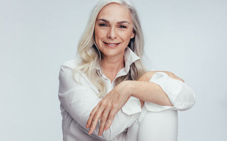 Photo pour Beautiful mature woman sitting over white background. Senior woman sitting relaxed in studio. - image libre de droit