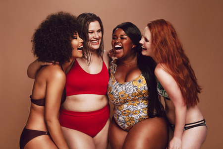 Photo pour Multi-ethnic women in swimwear having fun together in studio. - image libre de droit
