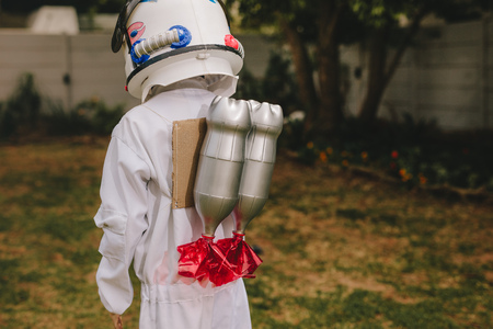 Photo pour Rear view of boy in space helmet and suit carrying a toy jetpack on his back. Boy pretending to be an astronaut playing outdoors. - image libre de droit