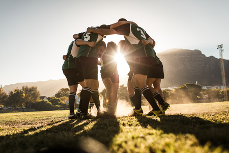 Photo pour Rugby team standing in a huddle and rubbing their feet on ground. Rugby team celebrating victory. - image libre de droit