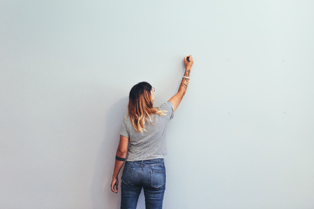Foto de Illustrator making a sketch on a wall. Rear view of a female creative artist writing on a wall . - Imagen libre de derechos