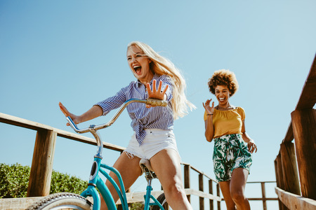 Foto de Excited girl cycling on a boardwalk with her friends running. Two woman friends enjoying themselves on the vacation. - Imagen libre de derechos