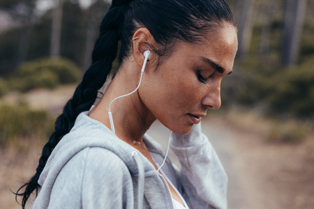 Foto per Side view of a female athlete wearing earphones listening to music. Sportswoman listening to music outdoors in morning. - Immagine Royalty Free