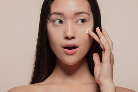 Photo pour Close up of a asian female model applying moisturizer to her face and looking away. Woman applying moisturizer cream on her pretty face against beige - image libre de droit