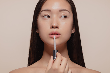 Foto de Portrait of beautiful young woman applying transparent lip gloss with applicator. Asian female model looking away while doing make up against beige background. - Imagen libre de derechos