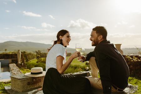 Photo pour Smiling couple sitting in a wine farm holding glasses of white wine. Couple on a date sitting in a vineyard with a picnic basket by their side. - image libre de droit